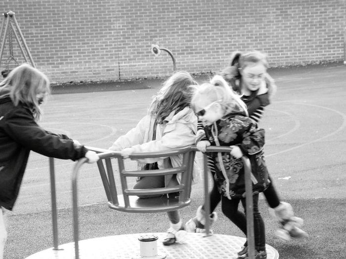 Children playing on merry-go-round at playground