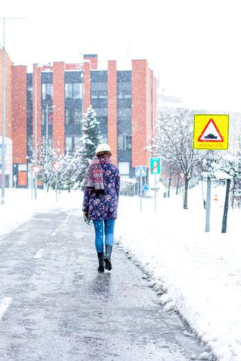 Full length rear view of man walking on snow