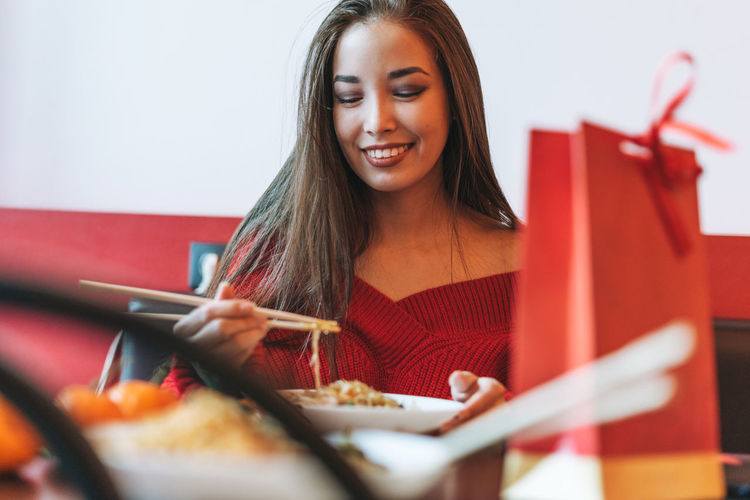 Asian woman in red clothes eating noodles with bamboo chopsticks in chinese vietnamese restaurant