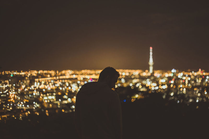 Rear view of silhouette man with illuminated cityscape against sky at night