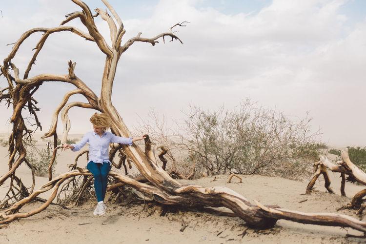 Woman sitting on dead tree