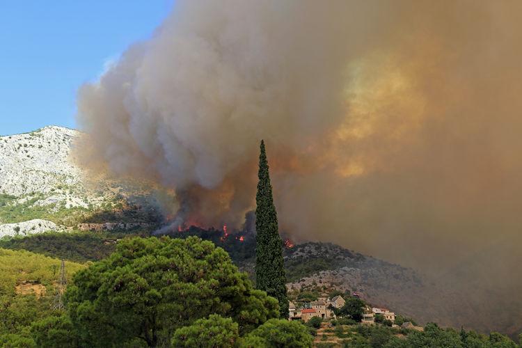 Panoramic view of smoke stacks against sky