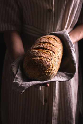 Woman holding a loaf of freshly baked bread