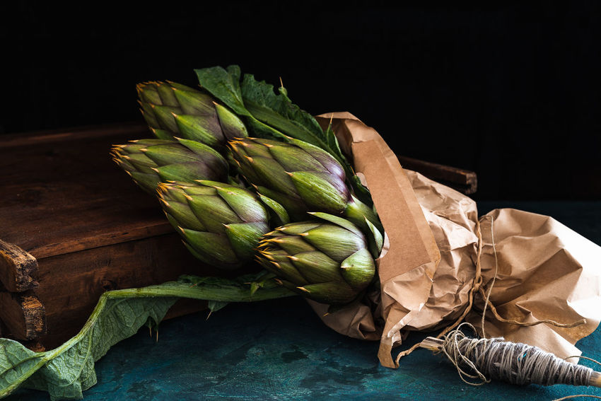 group of artichokes with leaves wrapped in a sheet of paper on rustic base Bundle Paper Bag String Vitamins Wrap Artichokes Chiaroscuro  Food Fresh Group Of Objects Healthy Food Leaf Organic Food Prickly Raw Food Rustic Background Still Life. Texture Thorny Thorny Plant Vegetable Garden Vegetable Garden In The Wintertime Vegetables Wooden Background Wrapping