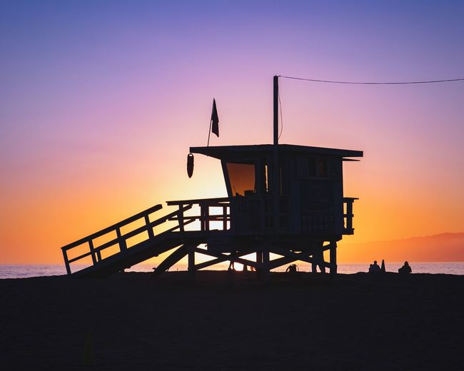Silhouette hut on beach against sky during sunset