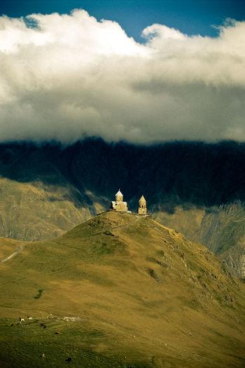 Gergeti trinity church on mountain against cloudy sky