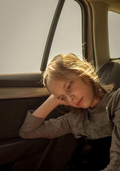 Girl looking away while sitting on window