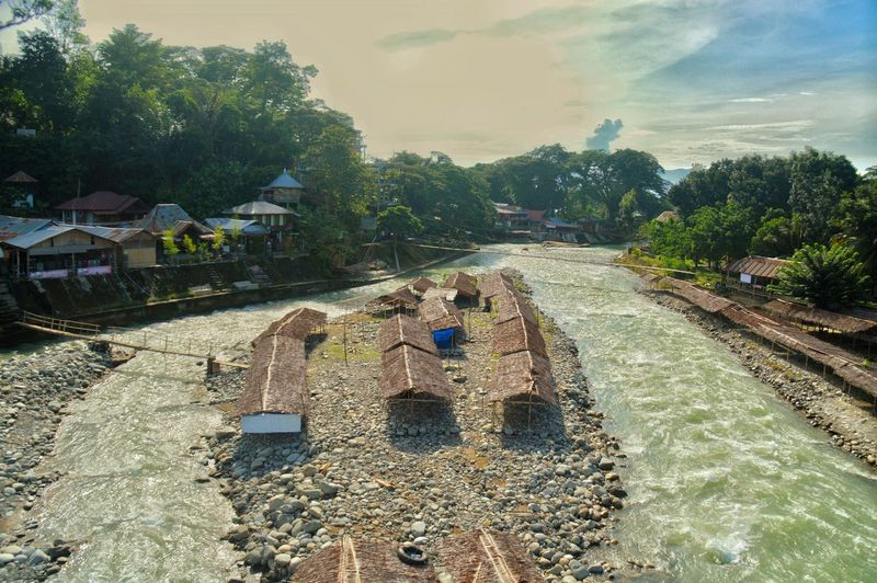 little islet in the middle of a river in Bukit Lawang, North Sumatra Day Outdoor Lifestyle Bukit Lawang North Sumatra INDONESIA Roofs Houses Village Islet Travel Off The Beaten Path Travel Adventure ASIA River Sky Tree Real People Nature
