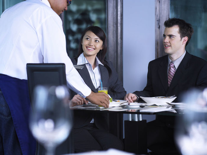 business couple work as team having lunch meeting Lunch Adult Business Businessman Cheerful Corporate Business Discussion Formal Businesswear Indoors  Lunch Meeting Meeting Men Occupation People Restaurant Sitting Smiling Suit Teamwork Togetherness Waiter Women Working Young Adult