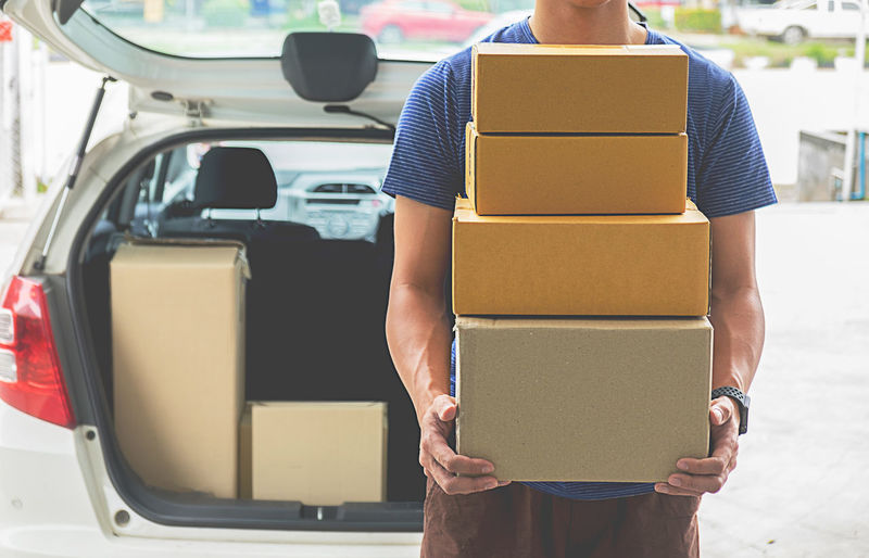 Midsection of delivery person holding stacked cardboard boxes against car
