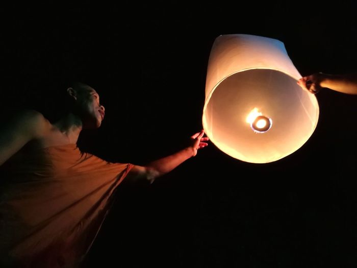 Low angle view of monk holding illuminated paper lantern against sky at night