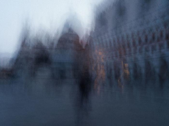 Defocused image of people walking on wet street