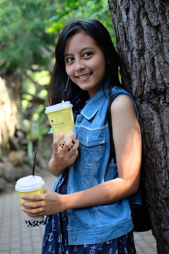 Smiling Girl With Disposable Cups Standing Against Tree
