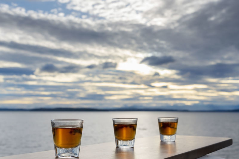 Three shots of alcohol over the sea in evening light outside deck view.