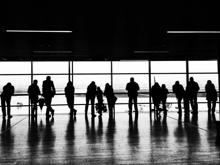 Silhouette People Standing At Window In Airport