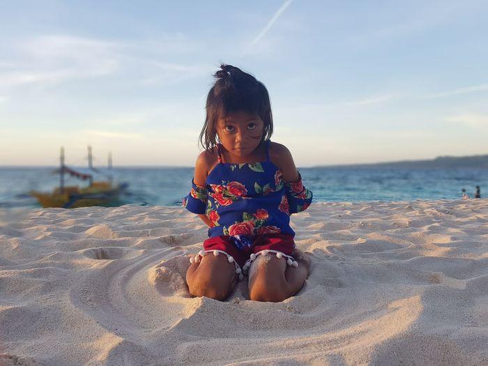 Portrait of girl kneeling on sand at beach against sky