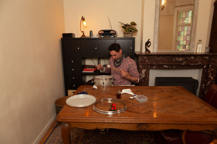 Young man using laptop while sitting on table at home