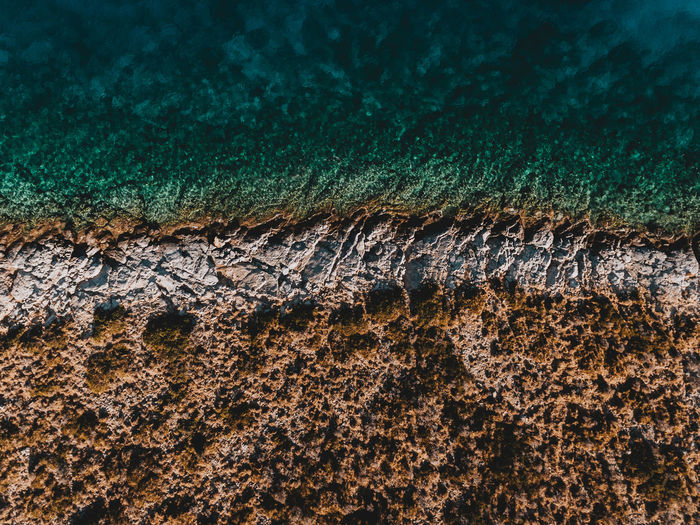 THE DIVIDE | @LostBoyMemoirs [Arid landscape meets the sea, split by the jagged rocky shoreline cutting into turquoise water. Greek landscapes always amaze. Taken with Sony A6300] Aerial Shot Drone  EyeEm Best Shots Landscape_Collection The Week on EyeEm Aerial Landscape Backgrounds Beauty In Nature Close-up Divide Dji Dronephotography Environment Land Ocean Pattern Sea Symmetry Textured  Tranquility Wallpaper
