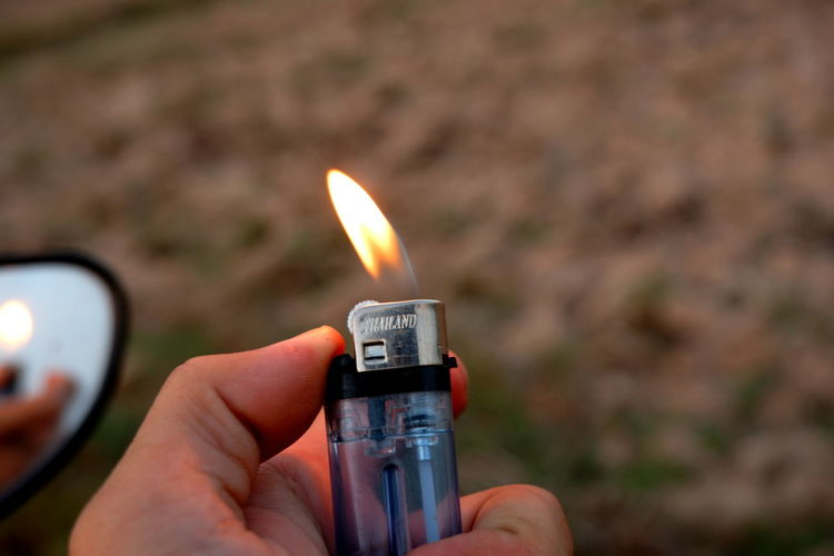 Close-up of hand holding burning cigarette lighter outdoors