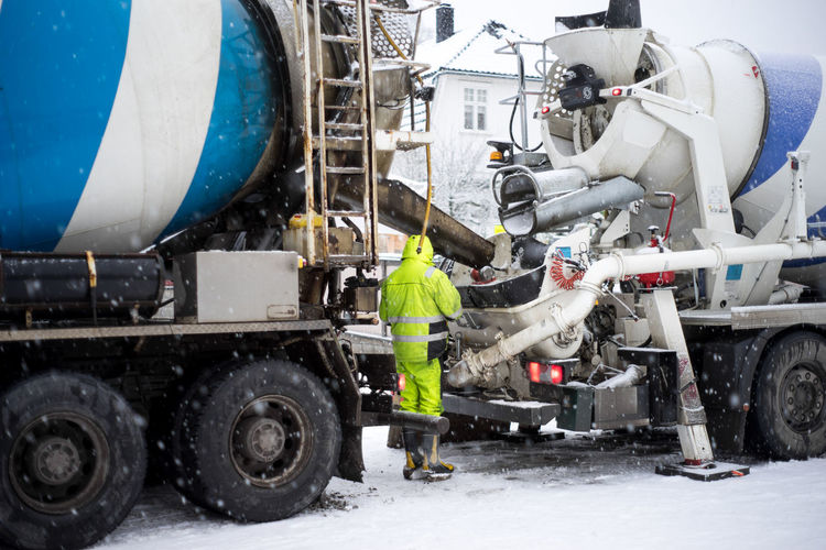 Rear view of man working while standing by cement mixer on snow covered field
