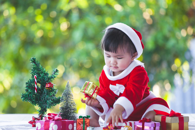 Full length of cute baby girl wearing santa costume while sitting with christmas decorations on table against trees