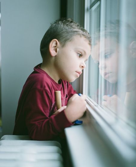 Thoughtful boy looking through window at home