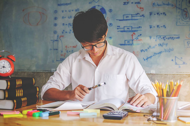 Man studying at desk against whiteboard