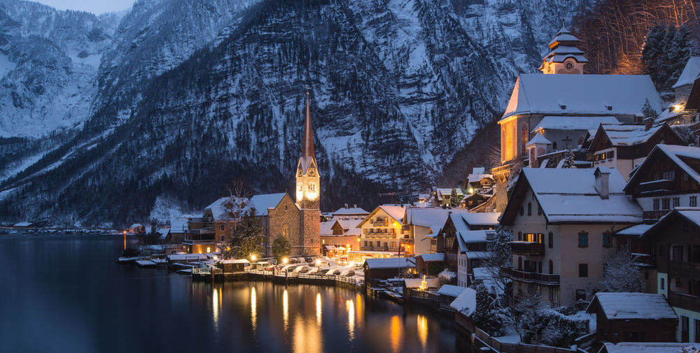 Buildings by lake during winter in hallstatt at dusk