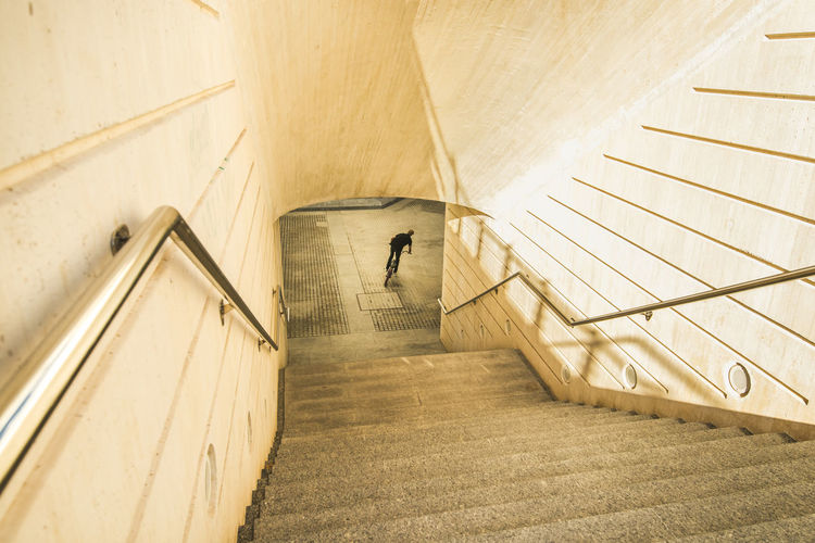 High angle view of man walking on staircase in building