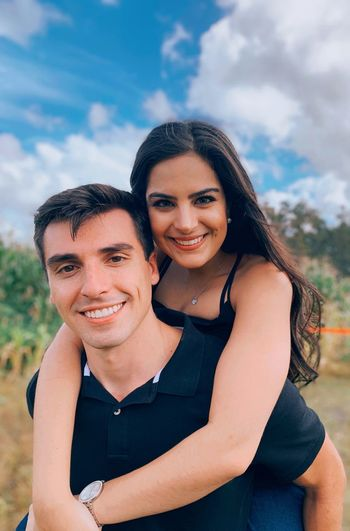 Portrait of smiling young couple against sky