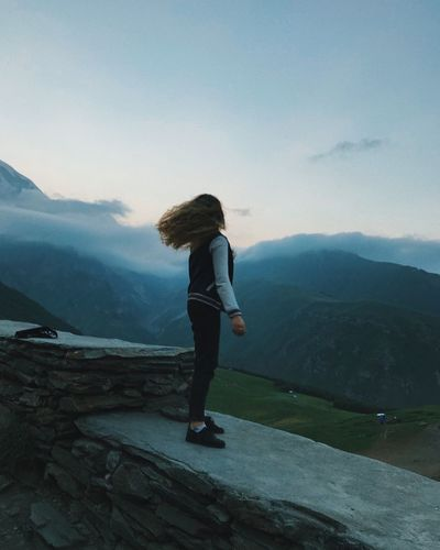Side view of young woman standing on mountain against sky during sunset
