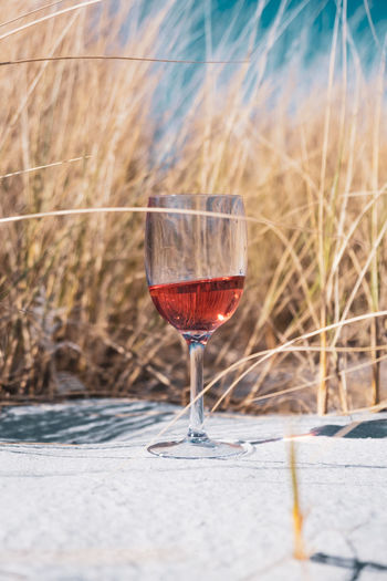 Close-up of a wine glass in sand in front of grass.
