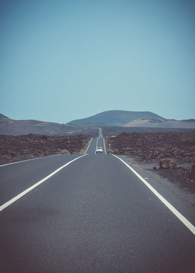 Lanzarote, Summer 2018 Arid Climate Clear Sky Climate Copy Space Day Diminishing Perspective Direction Environment Landscape Marking Mountain Nature No People Outdoors Road Road Marking Scenics - Nature Sign Sky Surface Level Symbol The Way Forward Tranquility Transportation vanishing point