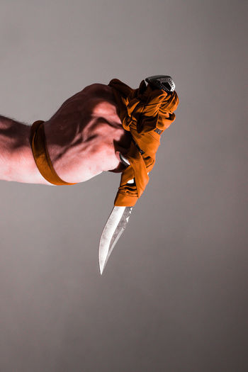 Close-up of hand holding weapon against gray background