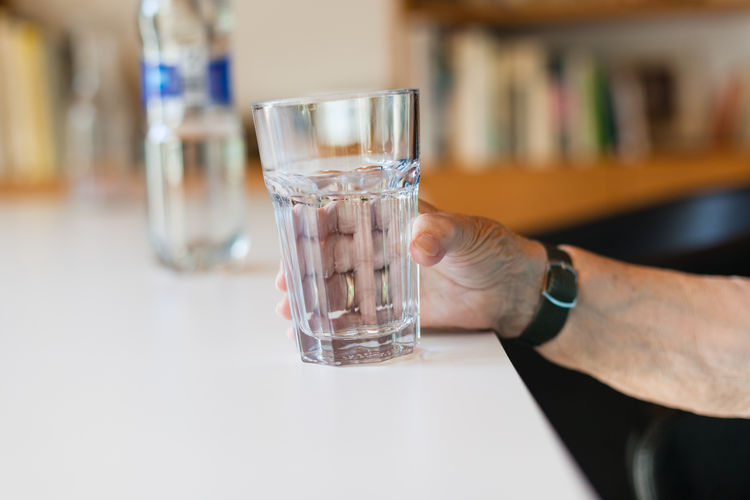 Close-up of man drinking glass with water