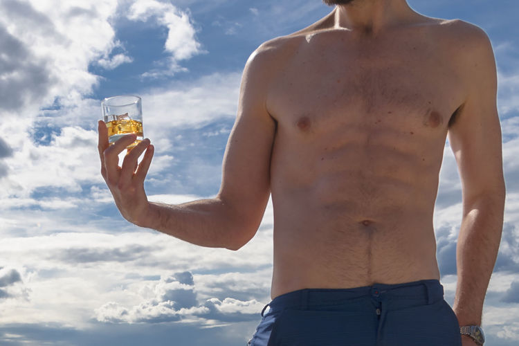 Midsection Of Shirtless Man Holding Glass Against Sky