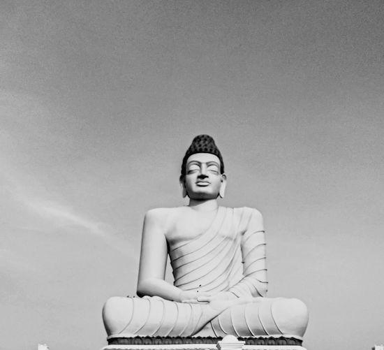 Portrait of a gauthama buddha sitting against wall