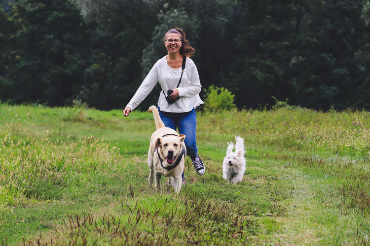 Young woman running with dogs on field