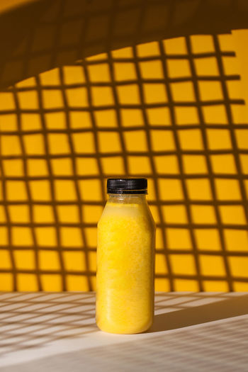 Smoothies of yellow color in a bottle on a yellow background with hard shadows.