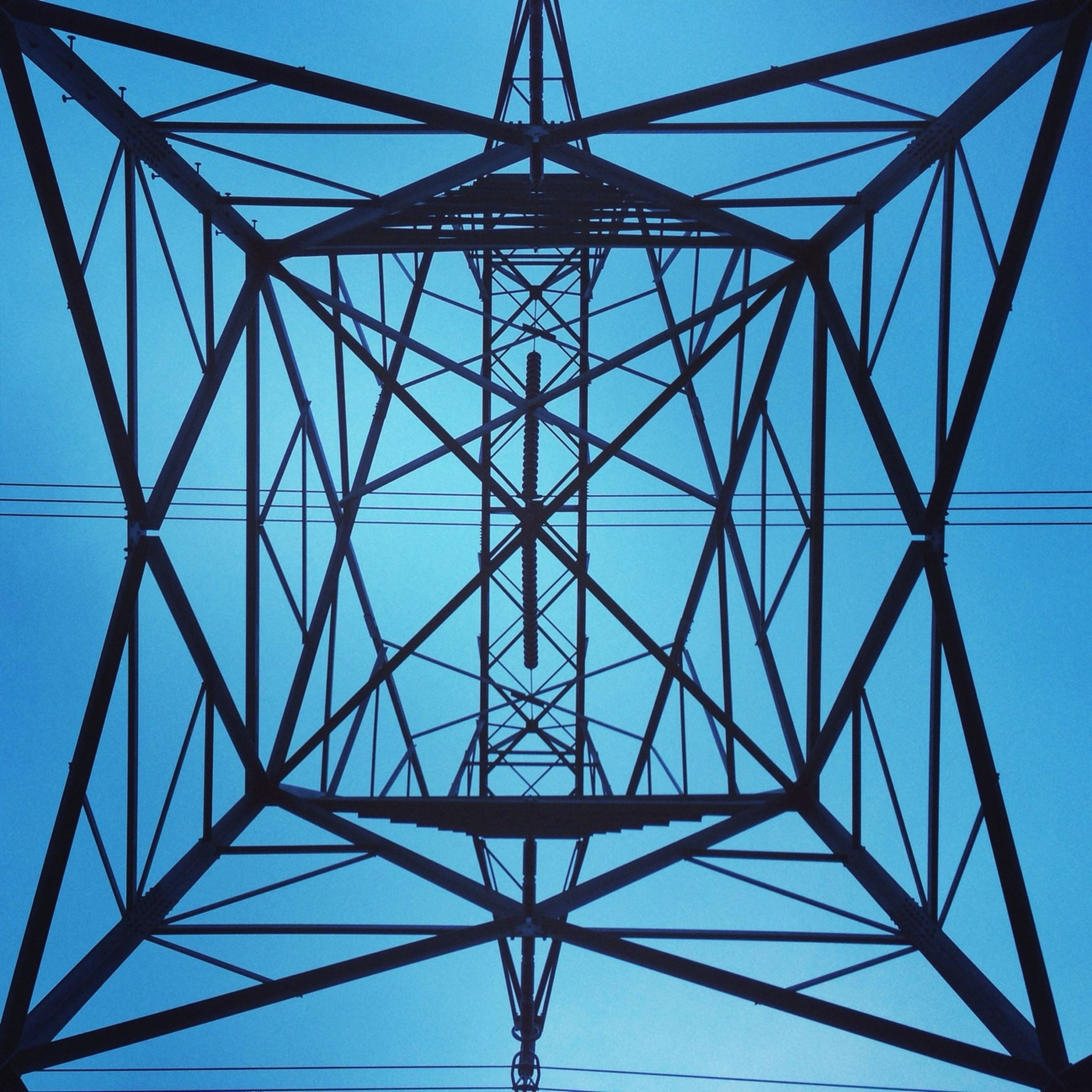 low angle view, power line, electricity pylon, connection, electricity, power supply, fuel and power generation, cable, technology, clear sky, sky, built structure, architecture, blue, complexity, metal, power cable, no people, outdoors, day