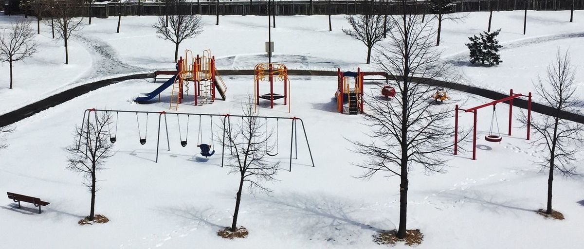 Swings Hanging At Snow Covered Park