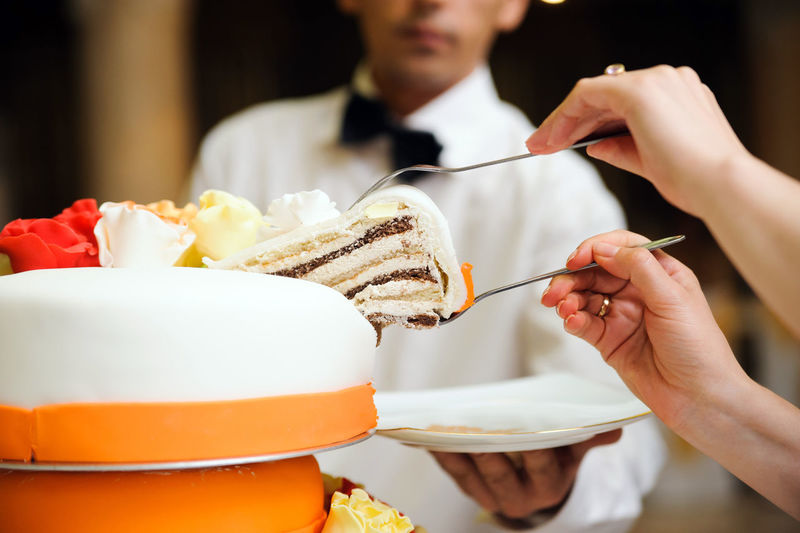 Cropped Image Of Woman Holding Forks With Cake By Waiter