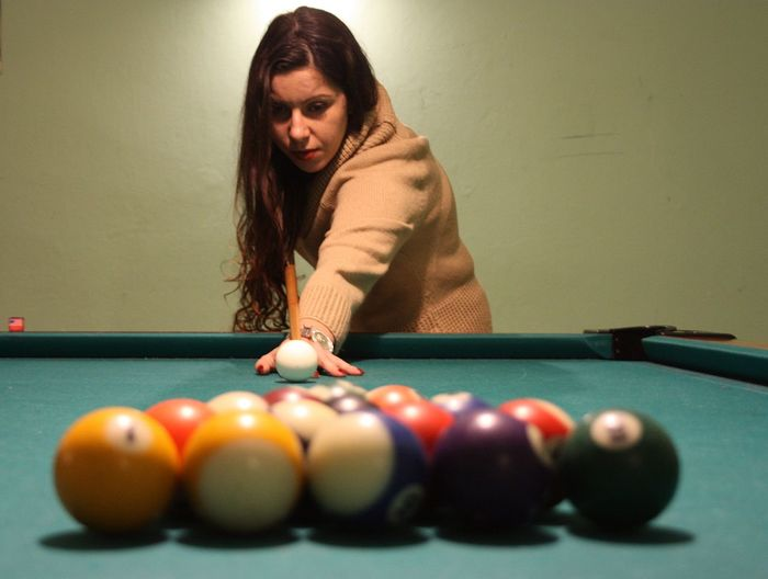 Young woman playing snooker