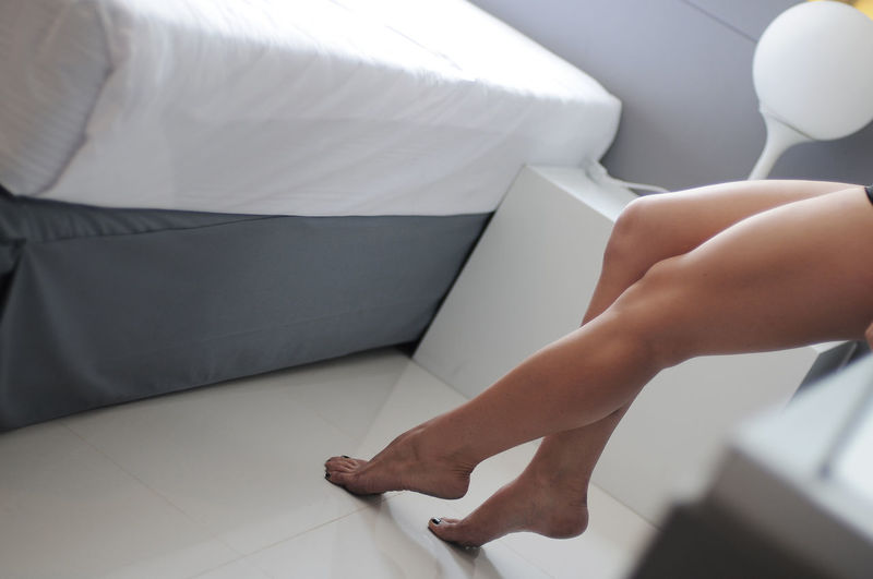 Low section of woman in bedroom