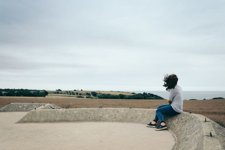 Teenager sitting on retaining wall against sky