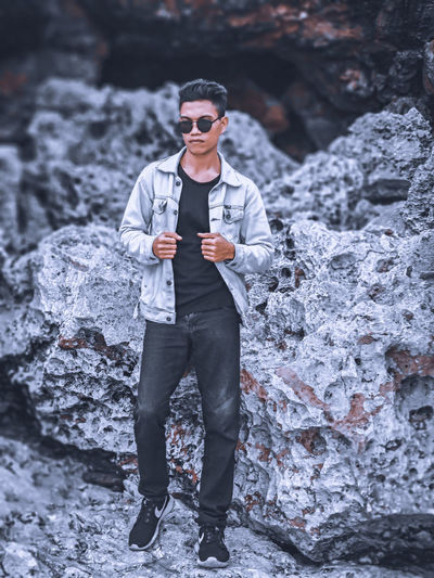 Full length of young man standing on rock