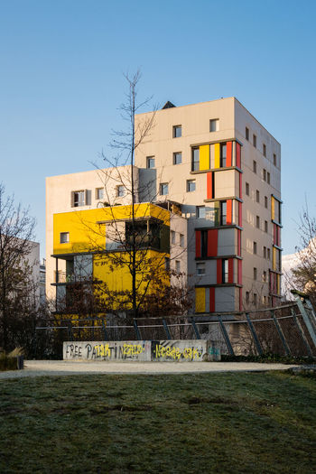 Morning light in Grenoble. Jardin de la Caserne de Bonne. 2019 - #06. Architecture Building Exterior Built Structure Residential District Residential Building Apartment Modern Colored Buildings Yellow Color Red Color Architectural Detail Façade Geometric Shape Lines And Shapes No People Morning Light Sunlight Blue Sky Low Angle View Copy Space Street Photography My Best Photo EyeEm Best Shots EyeEm Gallery