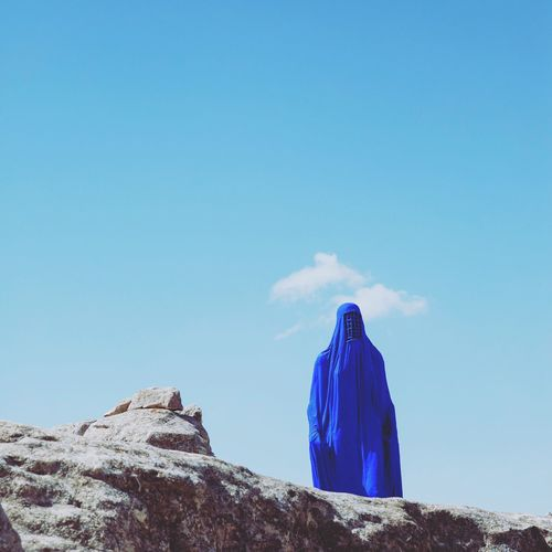 Low Angle View Of Woman In Burka Standing On Rock Formation Against Blue Sky During Sunny Day
