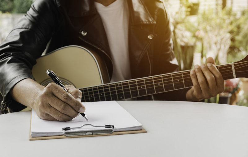 Midsection of man playing guitar on table