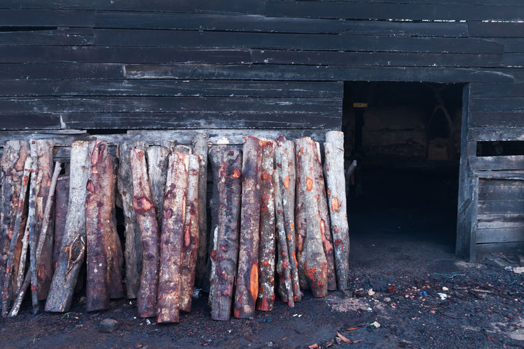 Logs arranged against warehouse